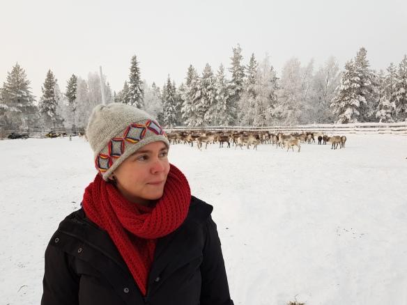 Jag (Sara) står framför en grupp renar, med snötäckta granar i bakgrunden. Foto: Annie Sundbäck
