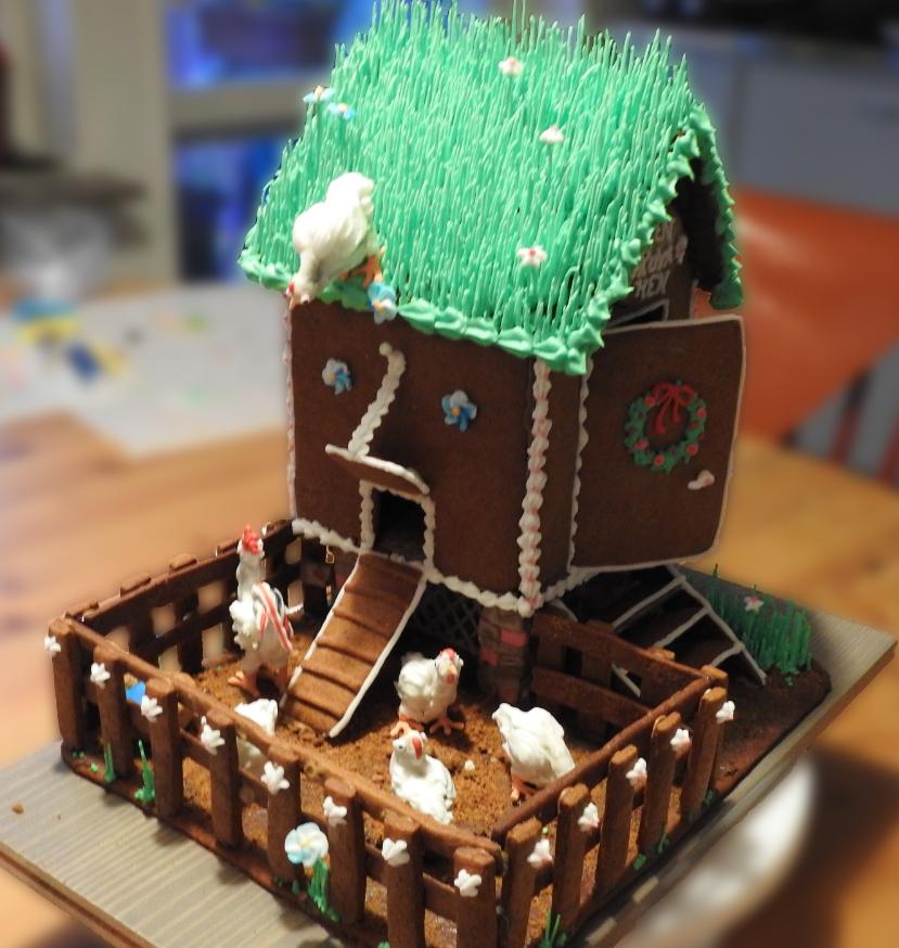 Ett pepparkakshönshus med grästak av grön kristyr, och en utegård med staket runt. På taket står en höna och tittar ner, och på gården finns fyra hönor och en tupp i kristyr. Huset och gården är dekorerade med blommor i vit, rosa och blå kristyr.