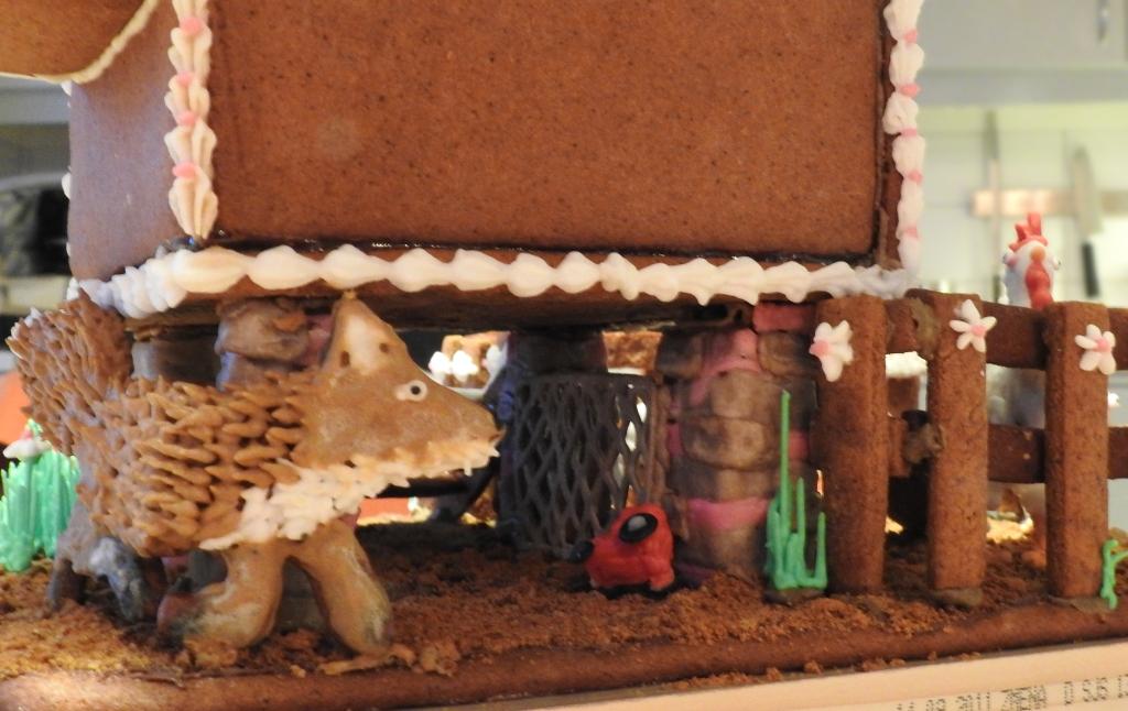 Bild på nederdelen av hönshusets bortre hörn, där en räv i pepparkaka och kristyrpäls slinker runt hörnet, på väg mot hönsgården. Vid en av grundpelarna ligger en röd leksakstraktor i kristyr.